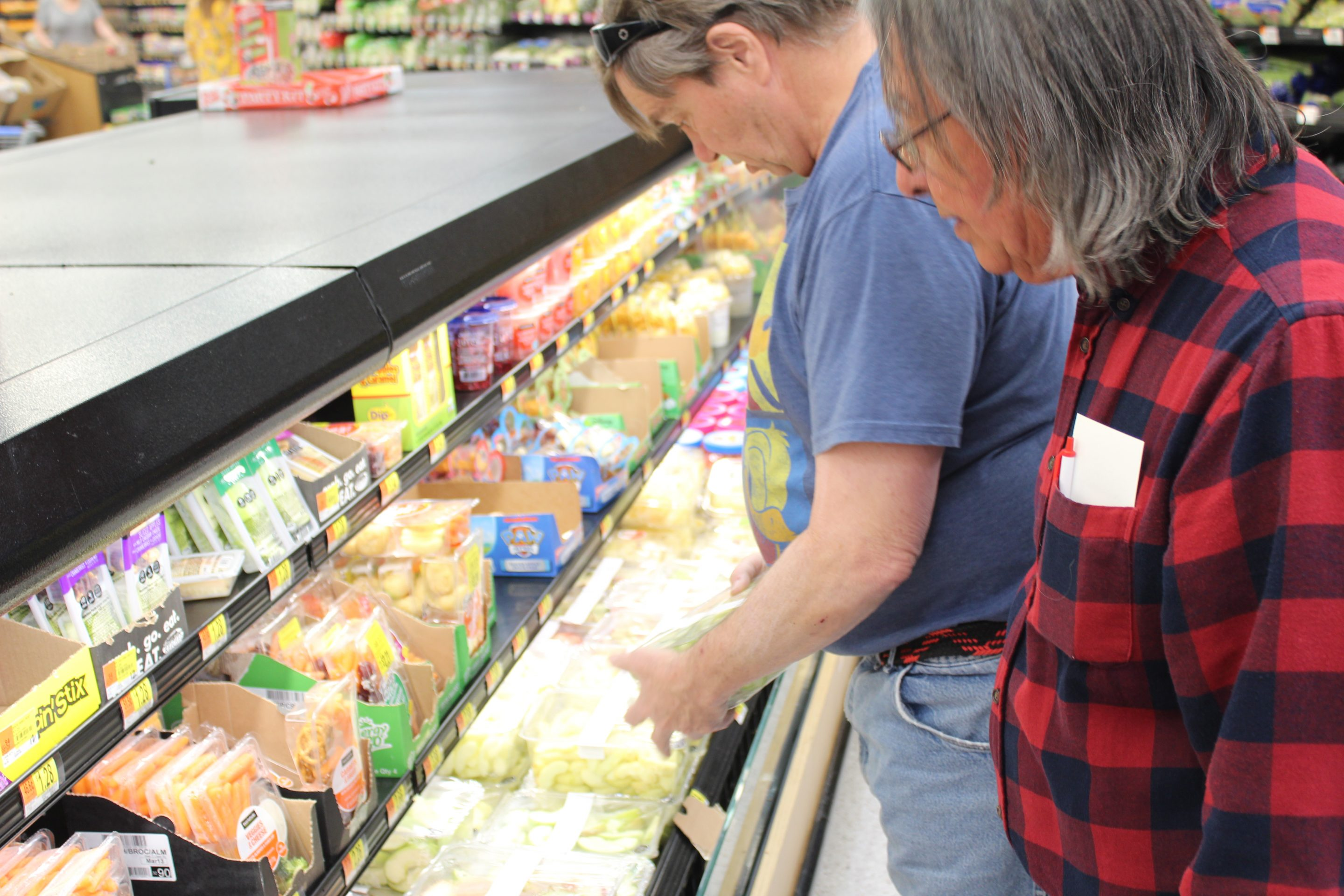 Mark and Dan both look down in a supermarket cooler to choose fruit. Mark is wearing a navy blue shirt and Dan is wearing and blue and red plaid shirt.