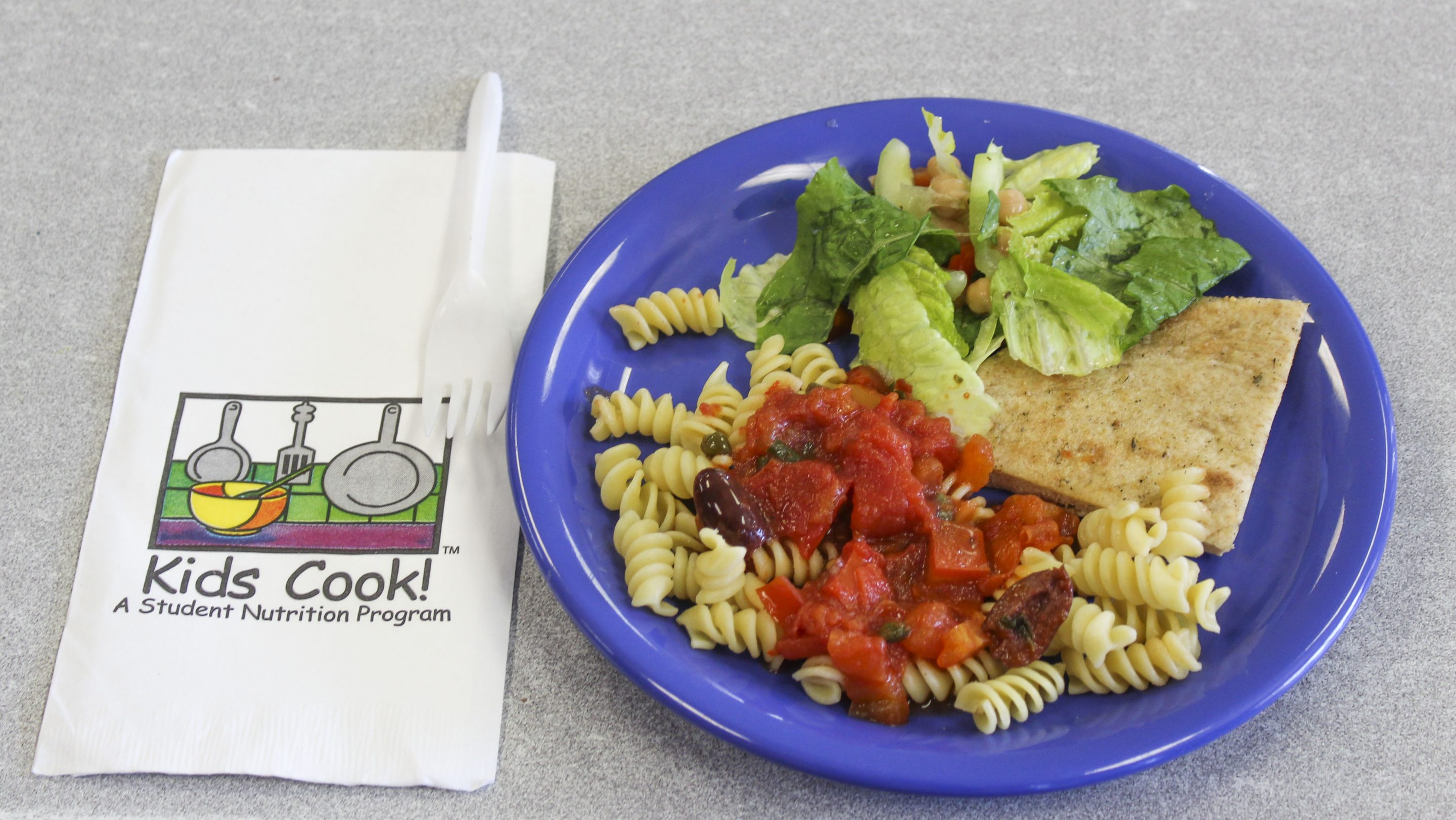 A blue plate with each of the dishes cooked. A napkin with the Kids Cook! logo and a fork is on the left.
