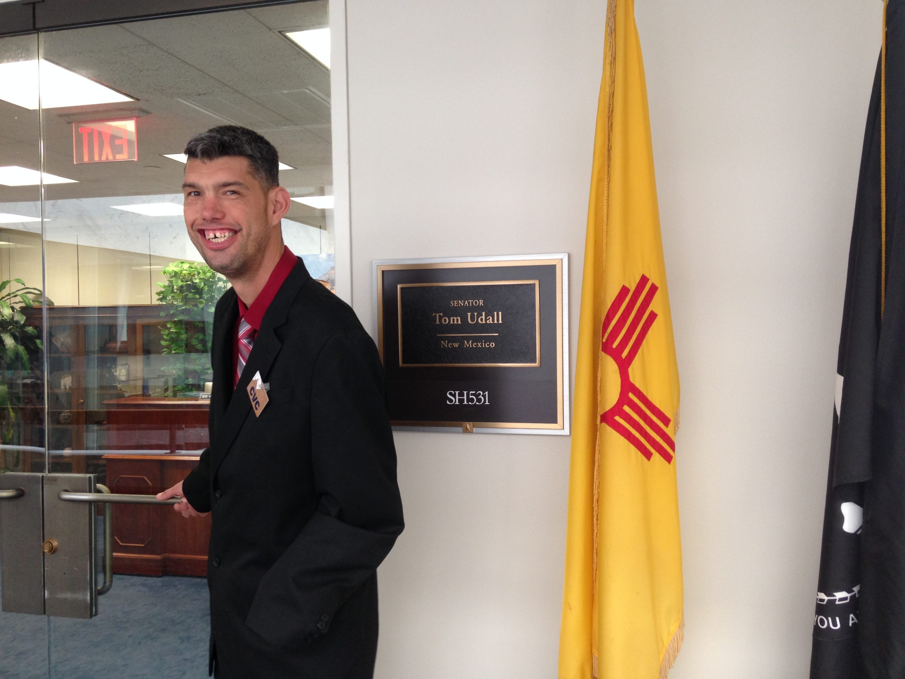 """A man in a dark suit smiles at the camera. He stands to the left of a sign that reads: """"Senator Tom Udall, New Mexico."""" To the left of the sign stand the New Mexico and POW flags."""