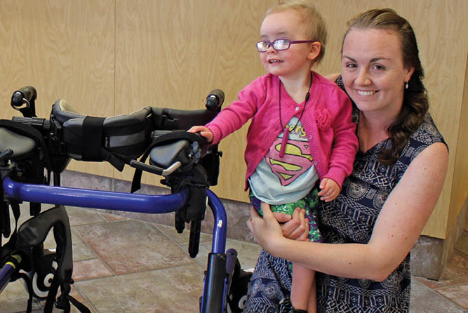woman with small child with a disability picks up a donated pediatric wheelchair