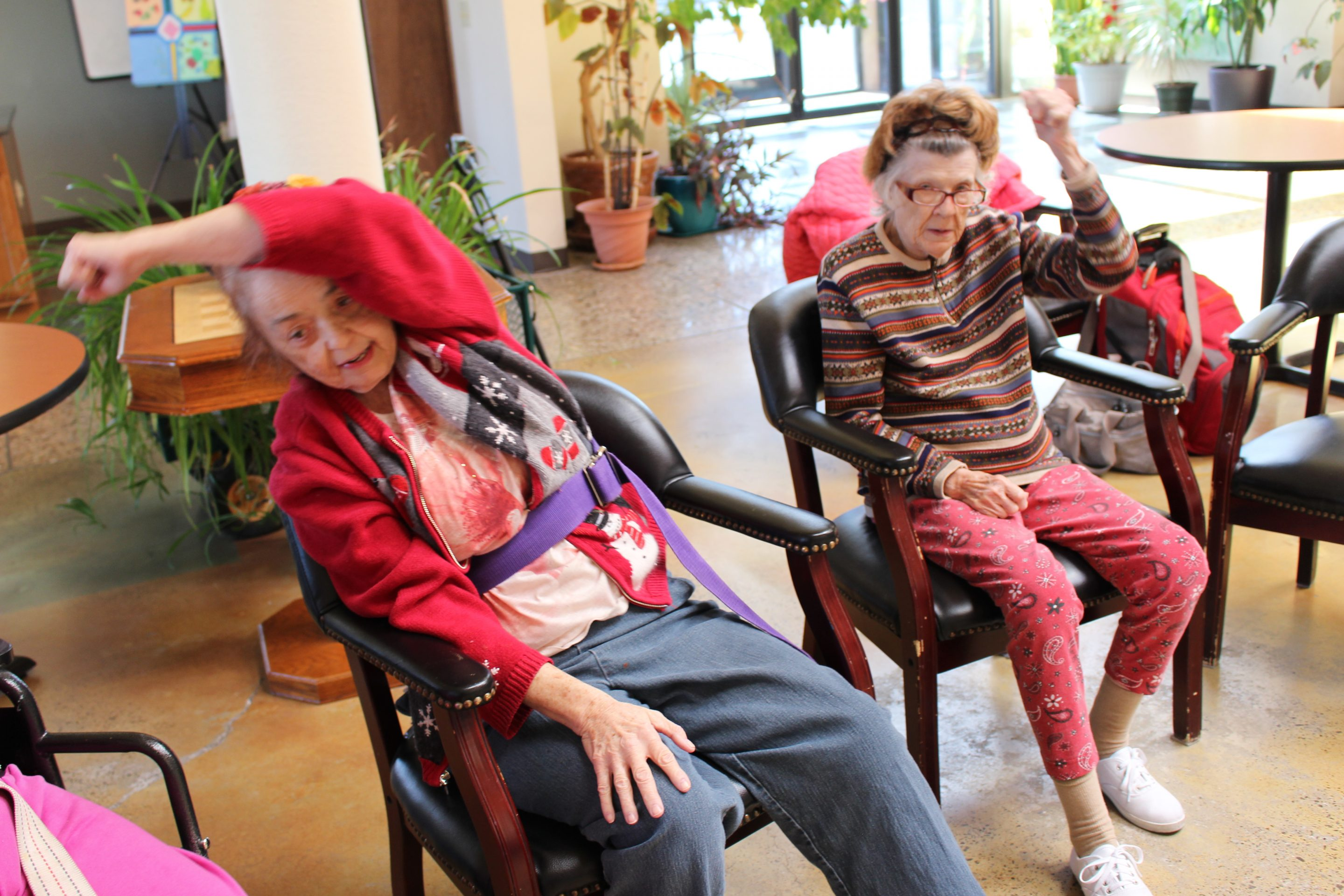 Two seniors at Compadres Senior Center doing chair exercises.