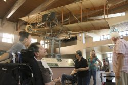 Clients and staff are viewing the 1914 Ingram-Foster Biplane that hangs on the ceiling of the Sunport lobby.
