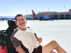 One of the clients in a wheelchair is posed in front of an airplane in the background