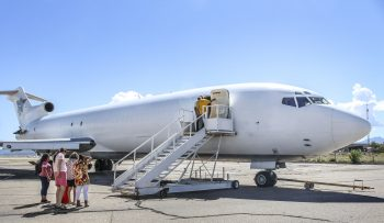 Clients to the right await to board the Boeing 727-200 plane