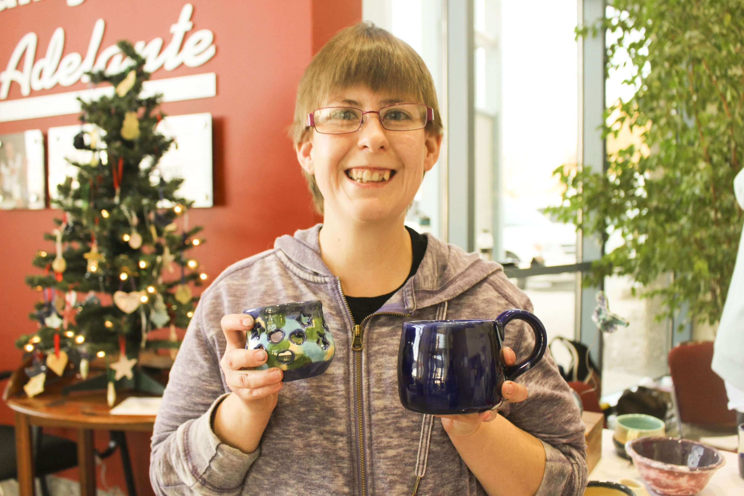 Jolene Blaylock, a client, holds up two of her mugs she created in the Arts & Animals program in the Adelante lobby