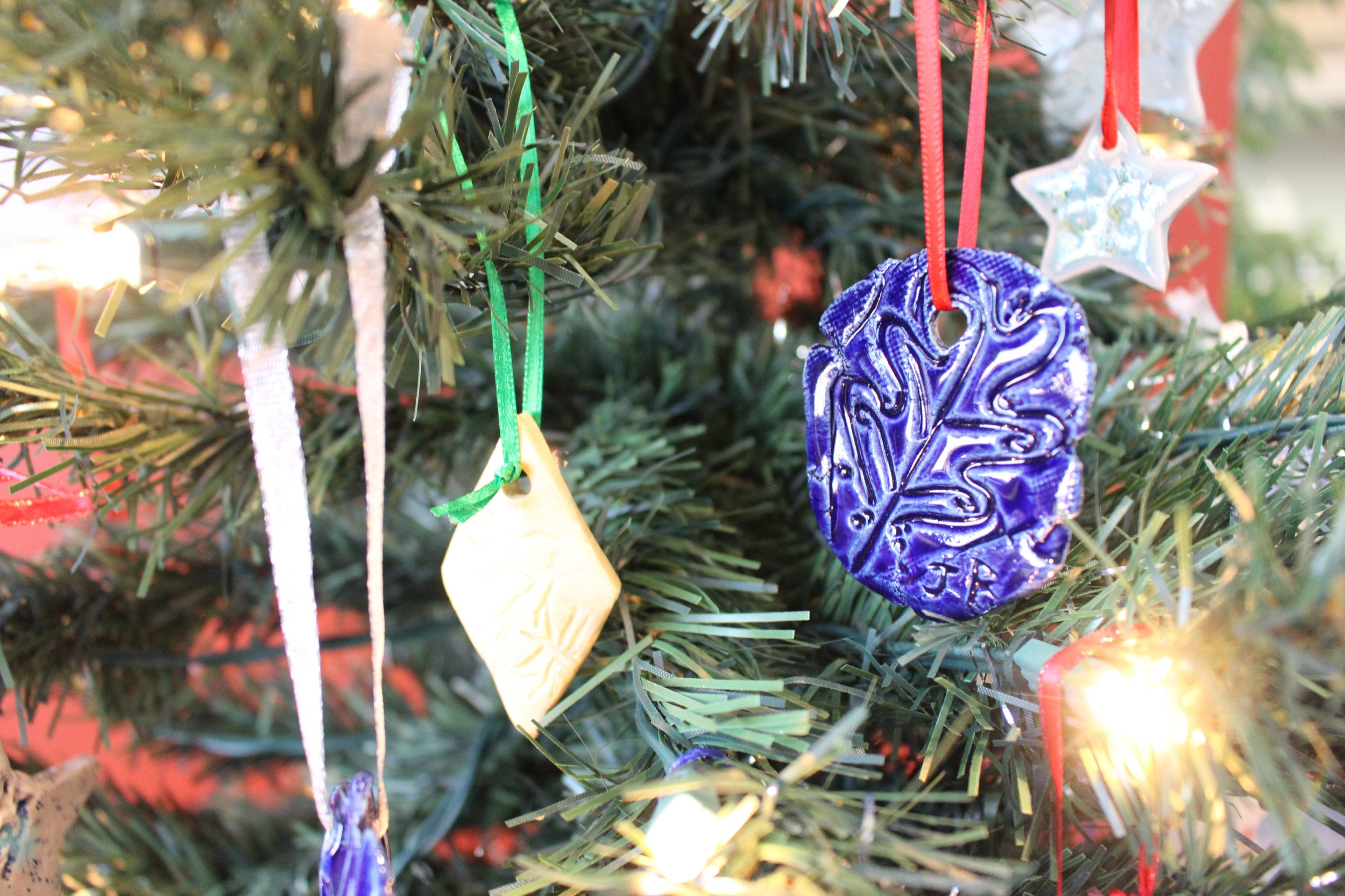 Photo showing blue, yellow, and turquoise ornaments. One ornament has a leaf design on it.