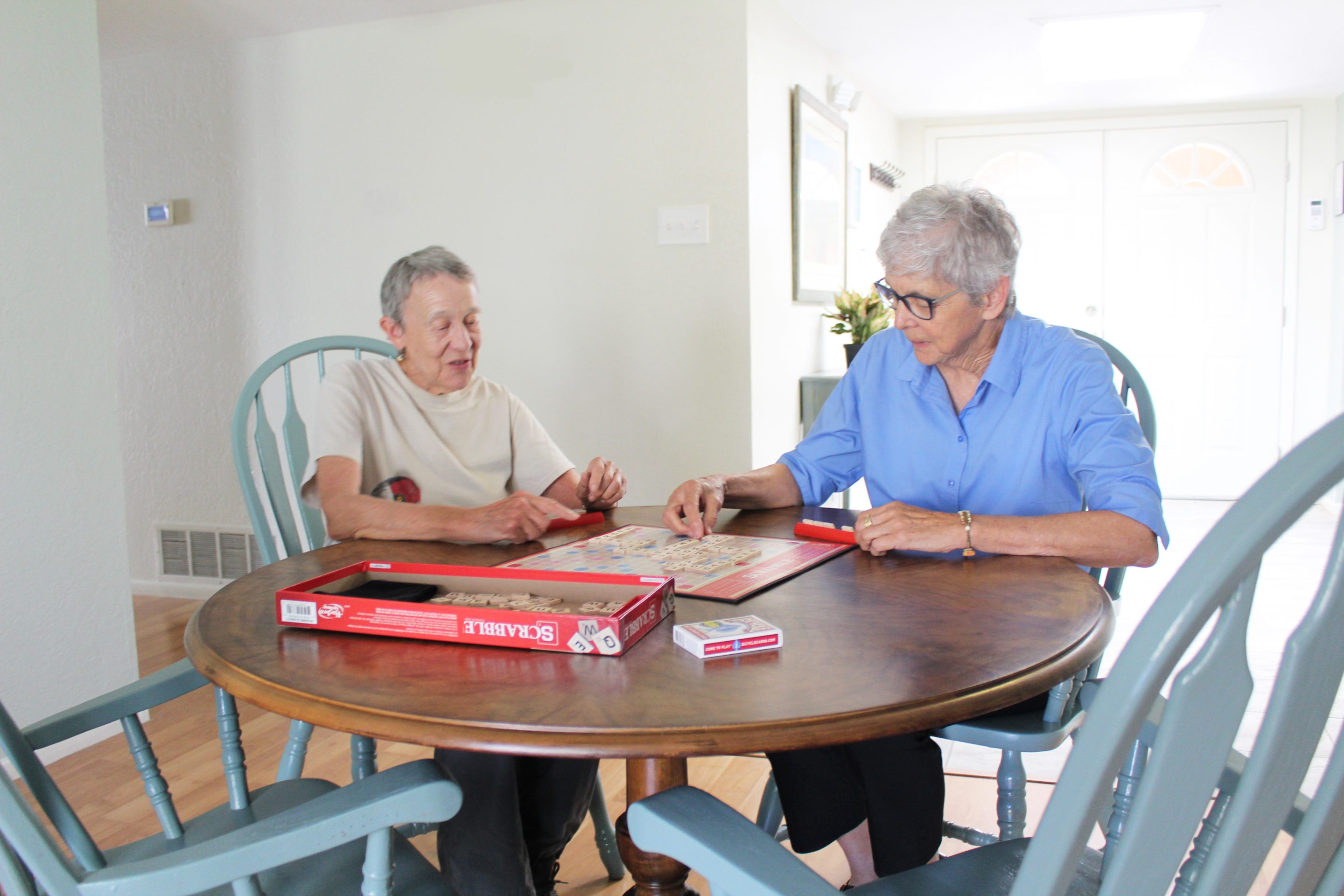 Two older women sit at a table playing scrabble
