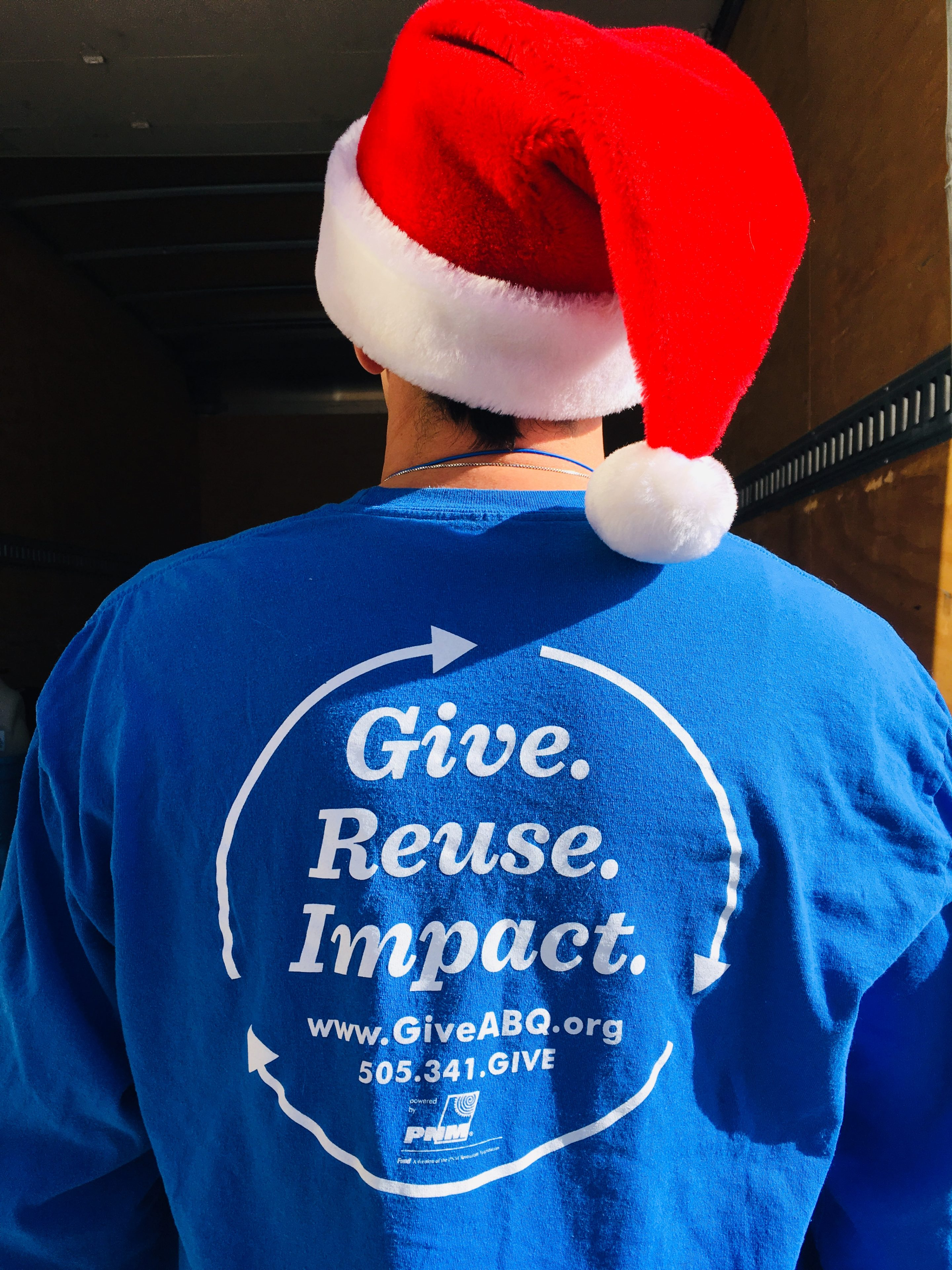 "Close-up of the back of a GiveABQ shirt that says ""Give. Reuse. Impact."" The wearer is donning a Santa hat"