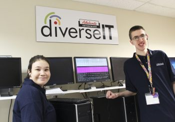 Two DiverseIT employees, with a computer in the process of refurbishing in between them. A sign with the DiverseIT logo hangs above them.