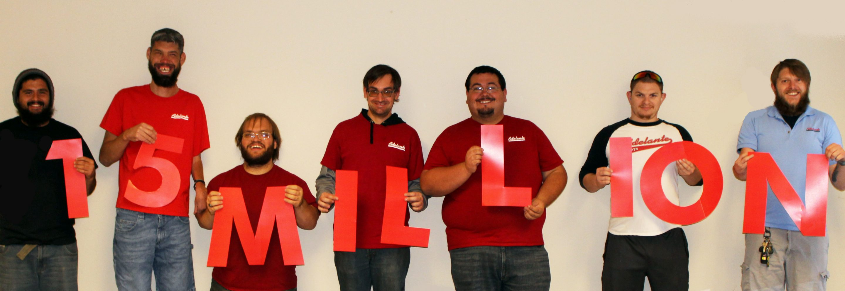 "Seven Bulk Printing and Mailing employes hold red numbers and letters that read ""15 MILLION."""