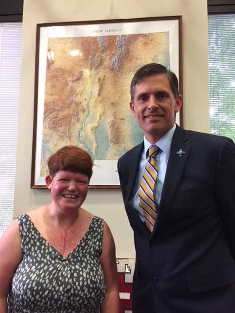Jessica and Senator Martin Heinrich smile for the camera. They are standing in front of a map of New Mexico.