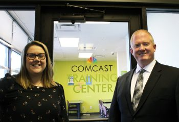 Comcast funders stand by the new door to a training room at DiverseIT Computer Repair and Training Center showing it is the Comcast Training Center. They are the sponsors of the large training room