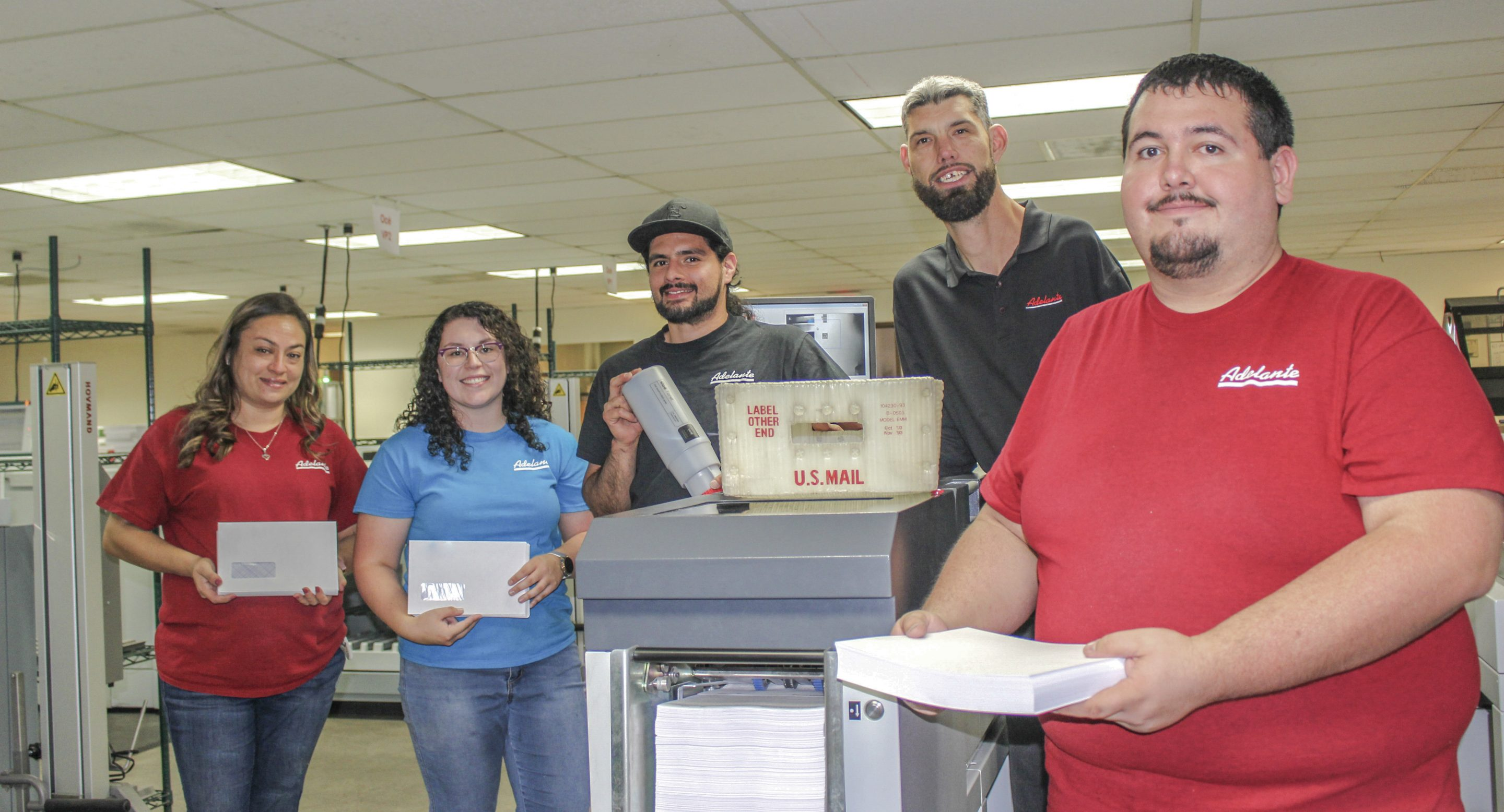 Five people are standing in a line around mailing equipment, smiling for the camera. There are two women on the left and three men on the right. They are holding mailing supplies.