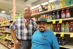 Two men stand together. Joe, the job coach, stands behind Jose, Adelante's supported employment participant. They are standing in front of a shelf with sports drinks and tea.