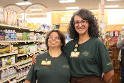Rosie is on the left and Stephanie is on the right. They are wearing their uniforms, and standing together and smiling. They are standing in the vitamin department at Sprouts.