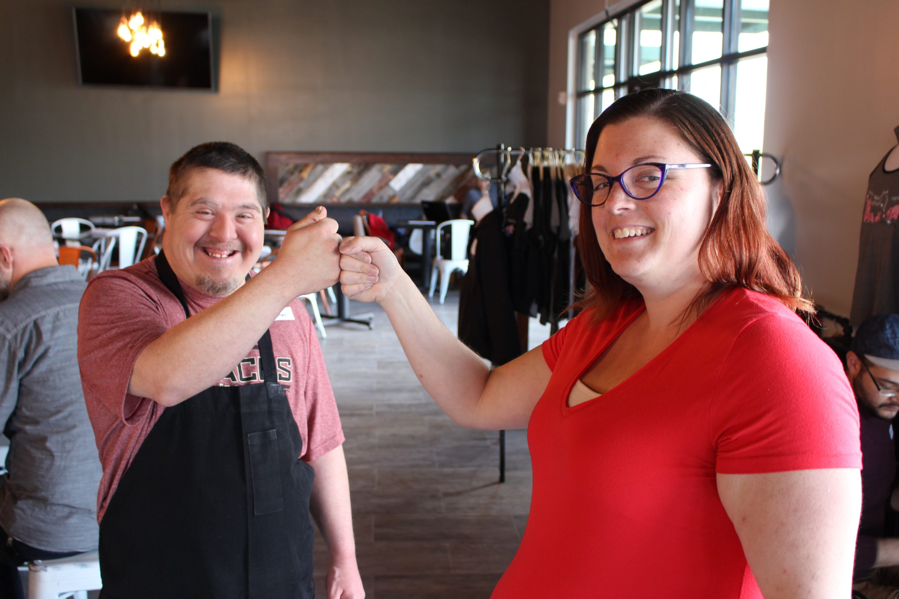A man and a woman fist bump and smile for the camera. The man, Stephen, just started his job working at a local restaurant.  Sarah supported him in being hired.