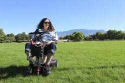 A woman sits on her scooter with her dog. They are in a grassy field surrounded by trees. It's sunny out. The Sandia Mountains are in the background.