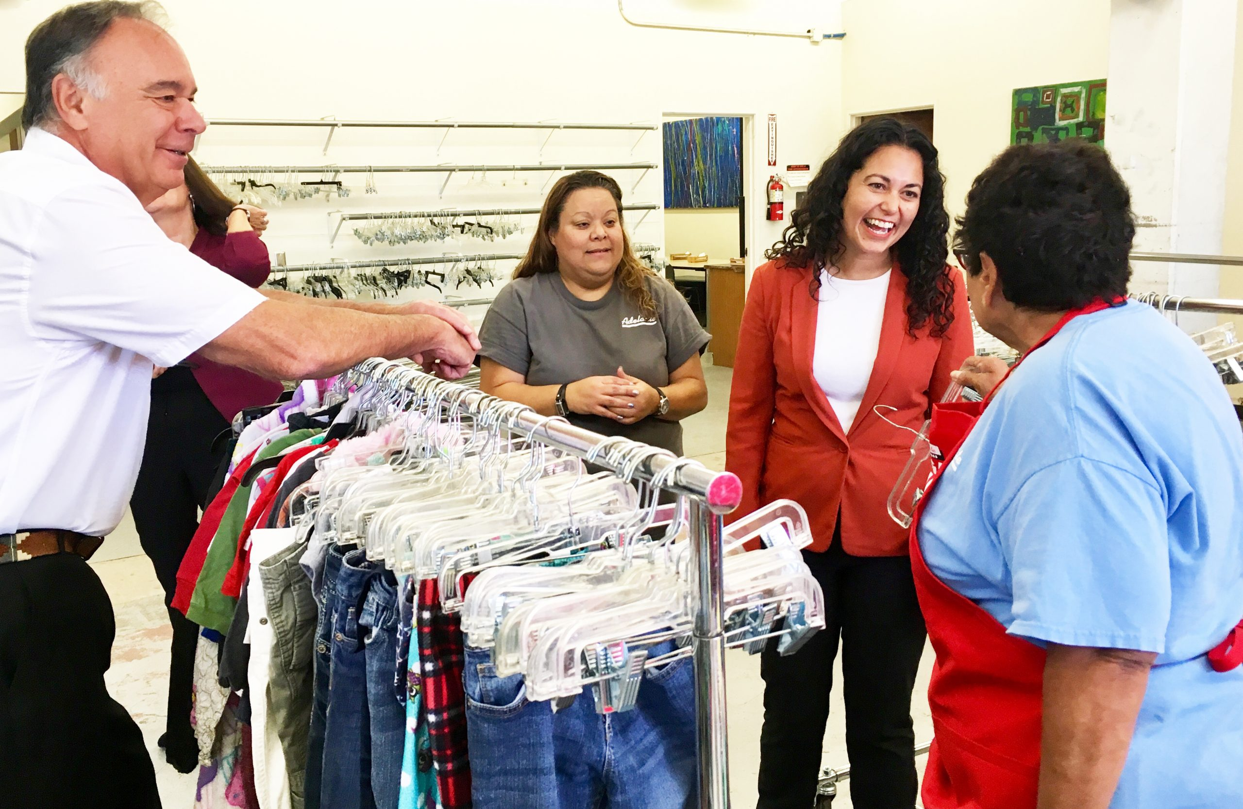 There are four people standing around a clothes rack. Congresswoman Xochitl Torres Small is smiling in the center. A client looks back at her. The Bargain Square manager stands behind Xochitl Torres Small. A man to the far left stands behind the clothes rack and smiles.
