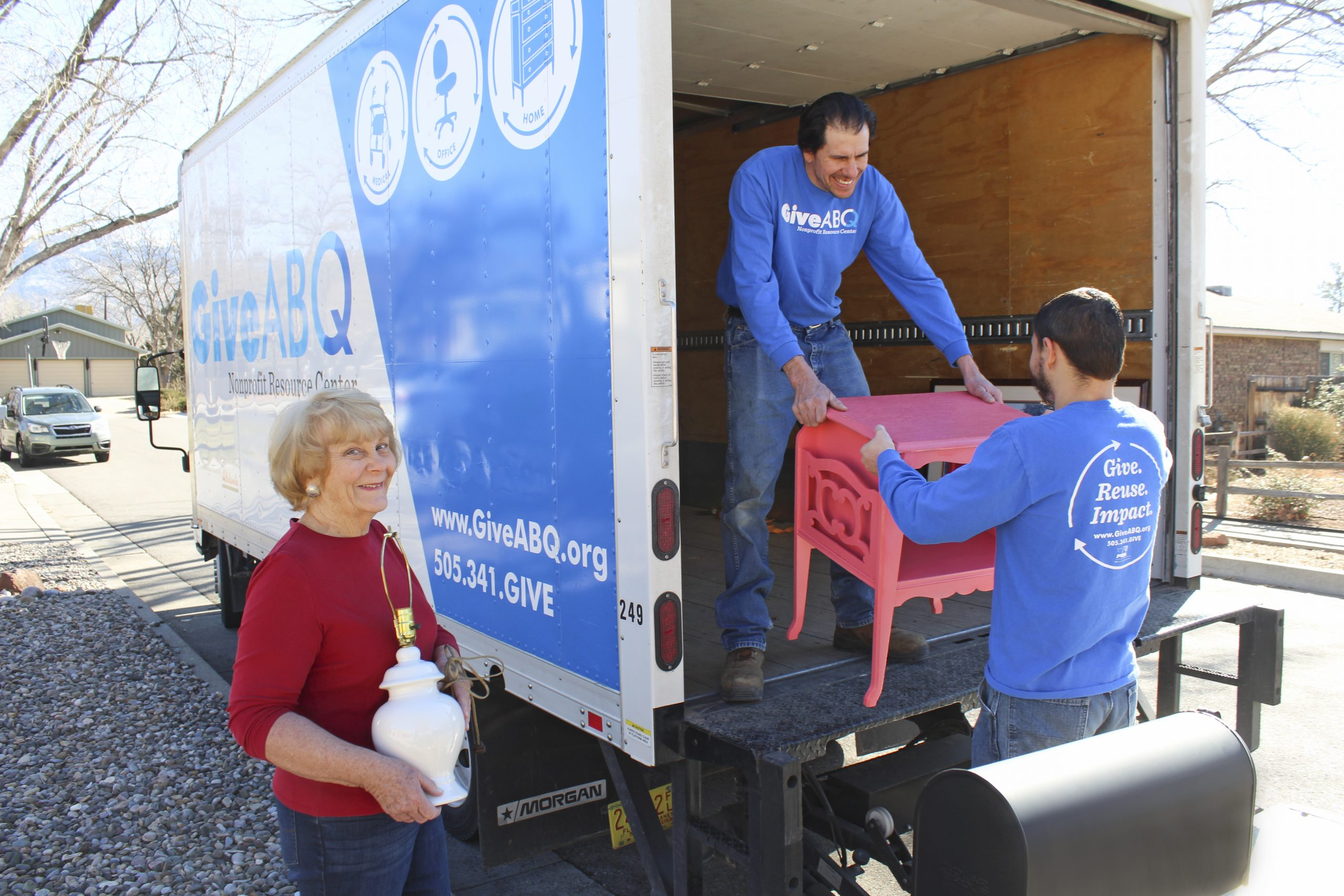 A woman stands to the left of a Give ABQ truck. She is holding a lamp. Two GiveABQ employees are loading a nightstand into the truck. The woman is smiling, happy t o be donating.