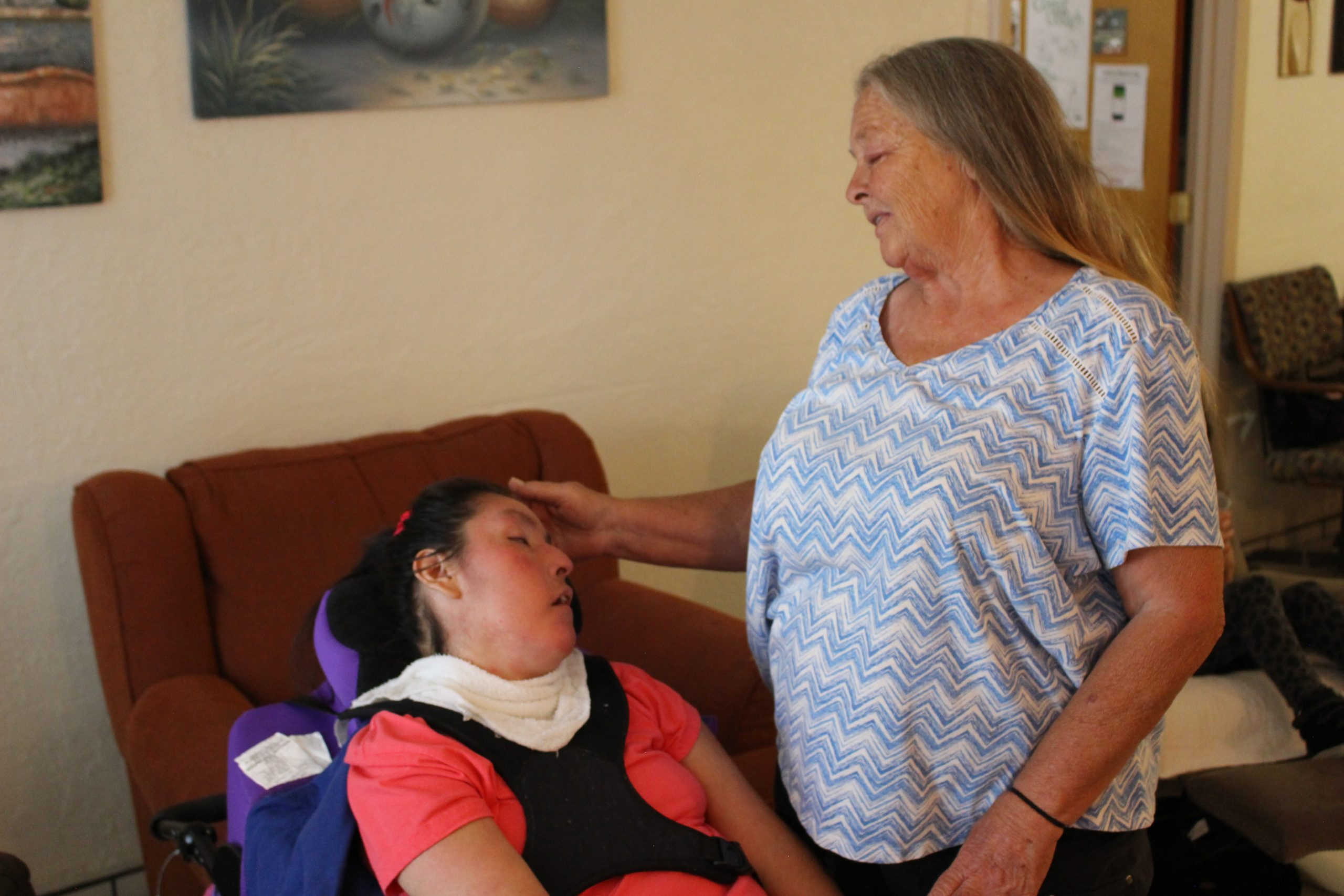 Two women are together in a living room. One uses an electric wheelchair. She is resting. Her support staff Cindy is standing next to her and checking on her.