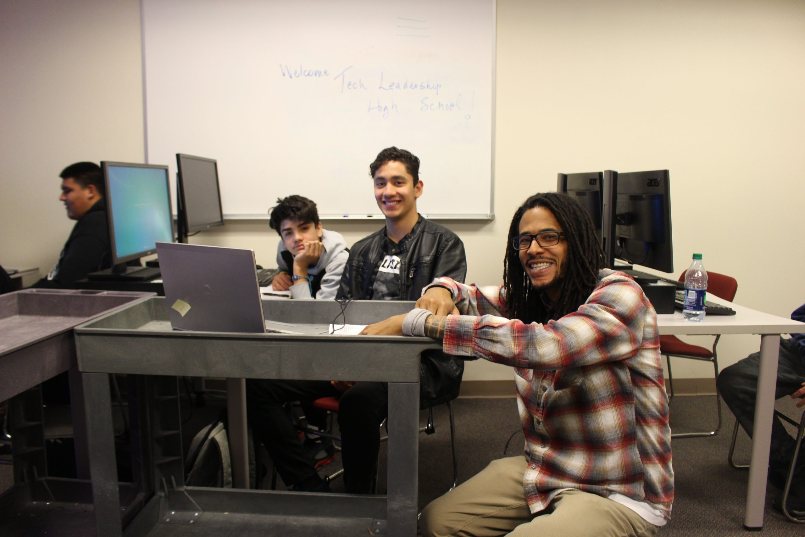 A man knells down and smiles next to two students working on computers. He is helping train them on technology.