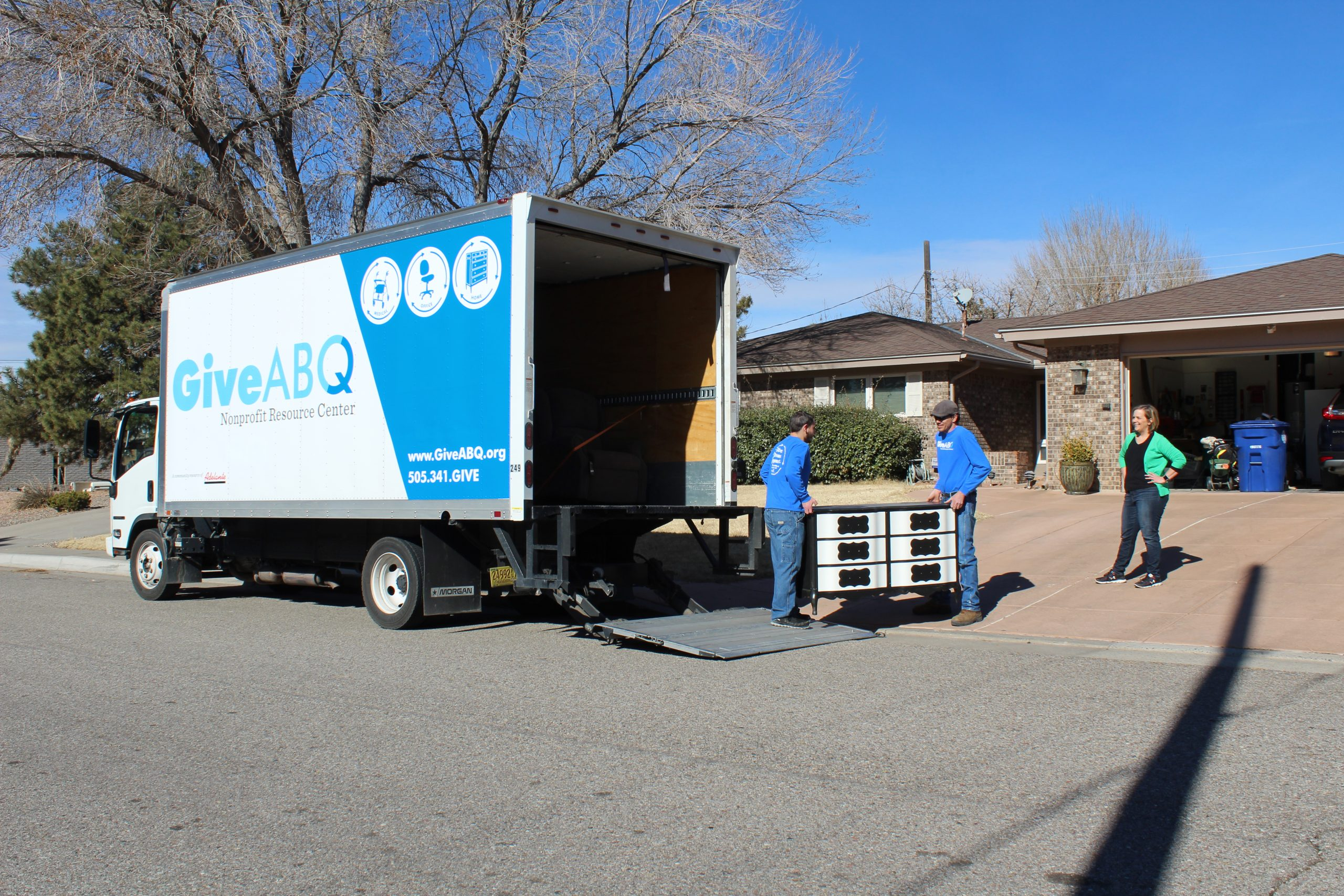 A woman stands in her driveway to the right of the GiveABQ truck watching the GiveABQ employees load a dresser that she is donating. She has her hand on her hips. She is happy that she is donating her dresser to GiveABQ.
