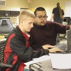 Two young men are sitting down and working on a computer together. Shawn is in the foreground traversing a computer with his hands. Anthony is in the background assisting him.