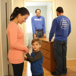 A mother is smiling down at her son. Two men from GiveABQ are behind them. They are delivering a dresser for them. The men are carrying the dresser into a bedroom.