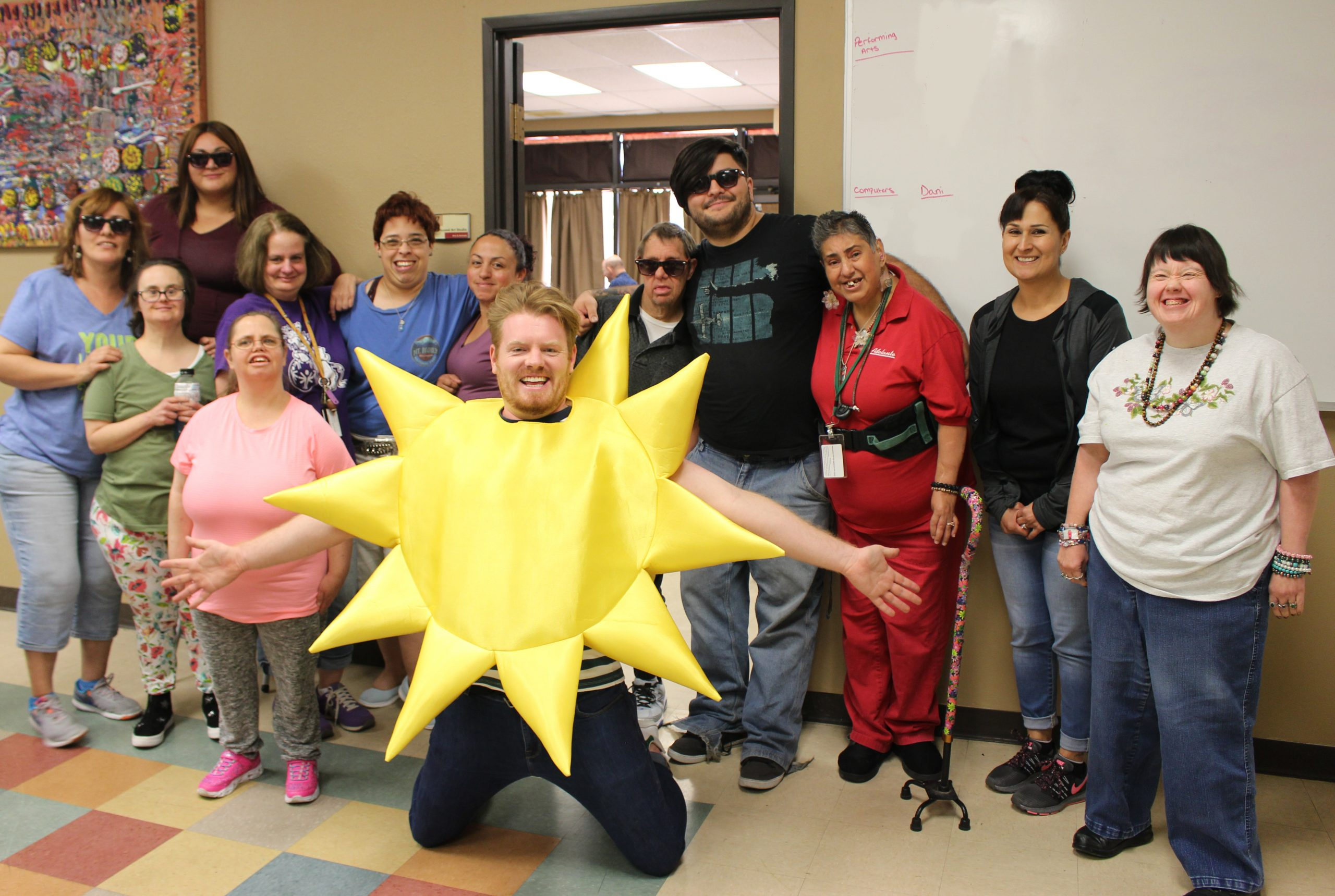 A man wearing a sun costume is kneeling in the center, smiling with his arms spread out. He is surrounded by smiling clients and other staff members.