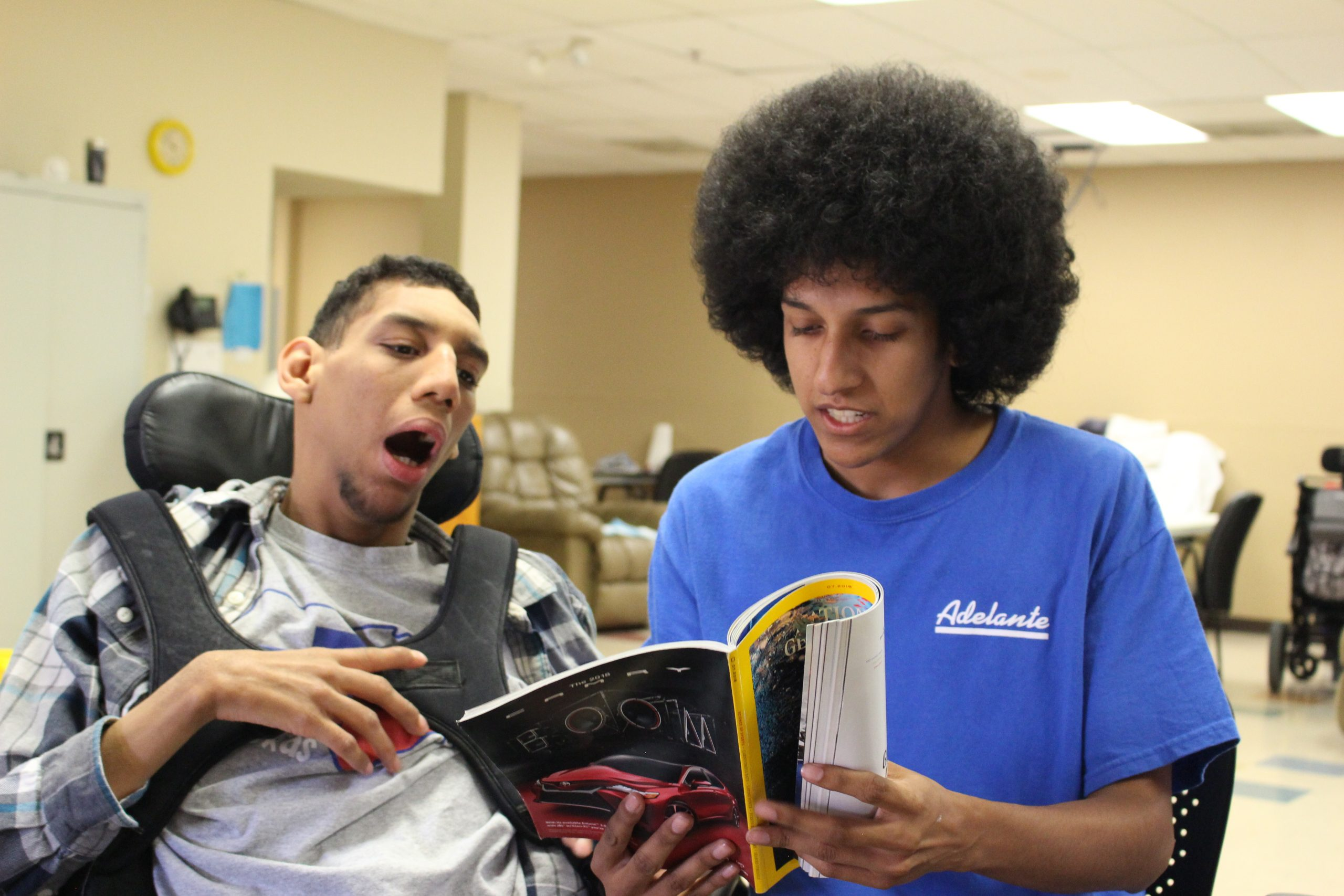 Two young men are sitting together. One is a direct support staff member. He's sitting next to his client and reading National Geographic to him. His client uses a wheelchair. The man who is an Adelante client reads with him.