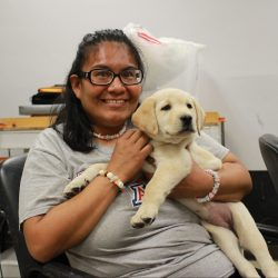 A woman is sitting down, smiling, and holding a Labrador puppy that she trains at Adelante's Arts and Animals program.