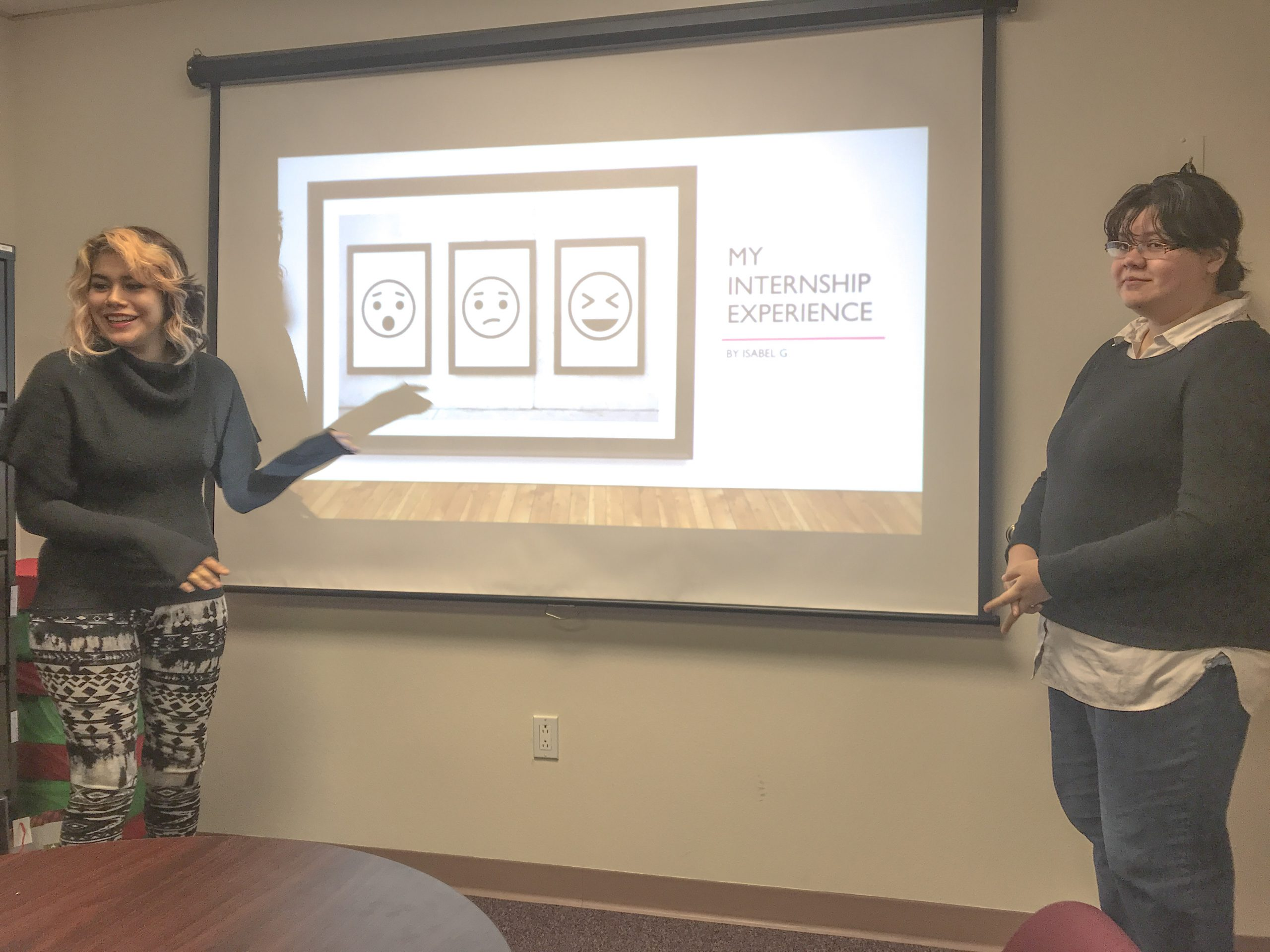 "Two girls are standing by a projection screen with a slide reading ""My Internship Experience."" Isabel is on the left, and she is gesturing toward the slide. Cassidy is on the right, looking at the viewers."