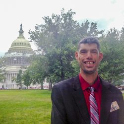 Pictured is Menard. He is a self advocate. He is wearing a suit and tie and standing in front of the Capitol Building in Washington, D.C. He is smiling for the camera.