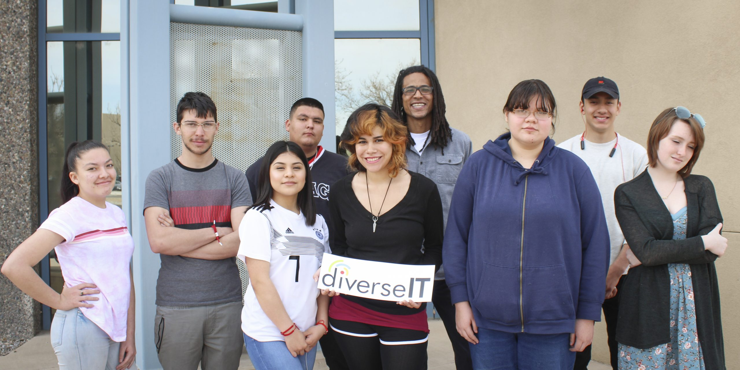 A group of nine people are standing together and posing for the camera. Isabel is in the center, fourth from the left; and Cassidy is also in the center, second from the right. Isabel is holding a sign with the DiverseIT logo. Jordan, the DiverseIT Program Manager, is standing in between and behind them. The other students are around them.