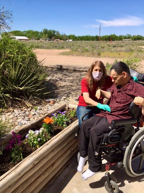 A man using a wheelchair is enjoying his accessible raised garden with a support staff member. To celebrate 30 years of the ADA, we want to point out how accessibility comes in a variety of forms.
