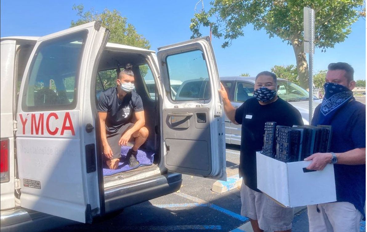 Three employees from the YMCA load donated computers from DiverseIT into their van. The employees are wearing masks. These computers will help students go back to school during COVID.