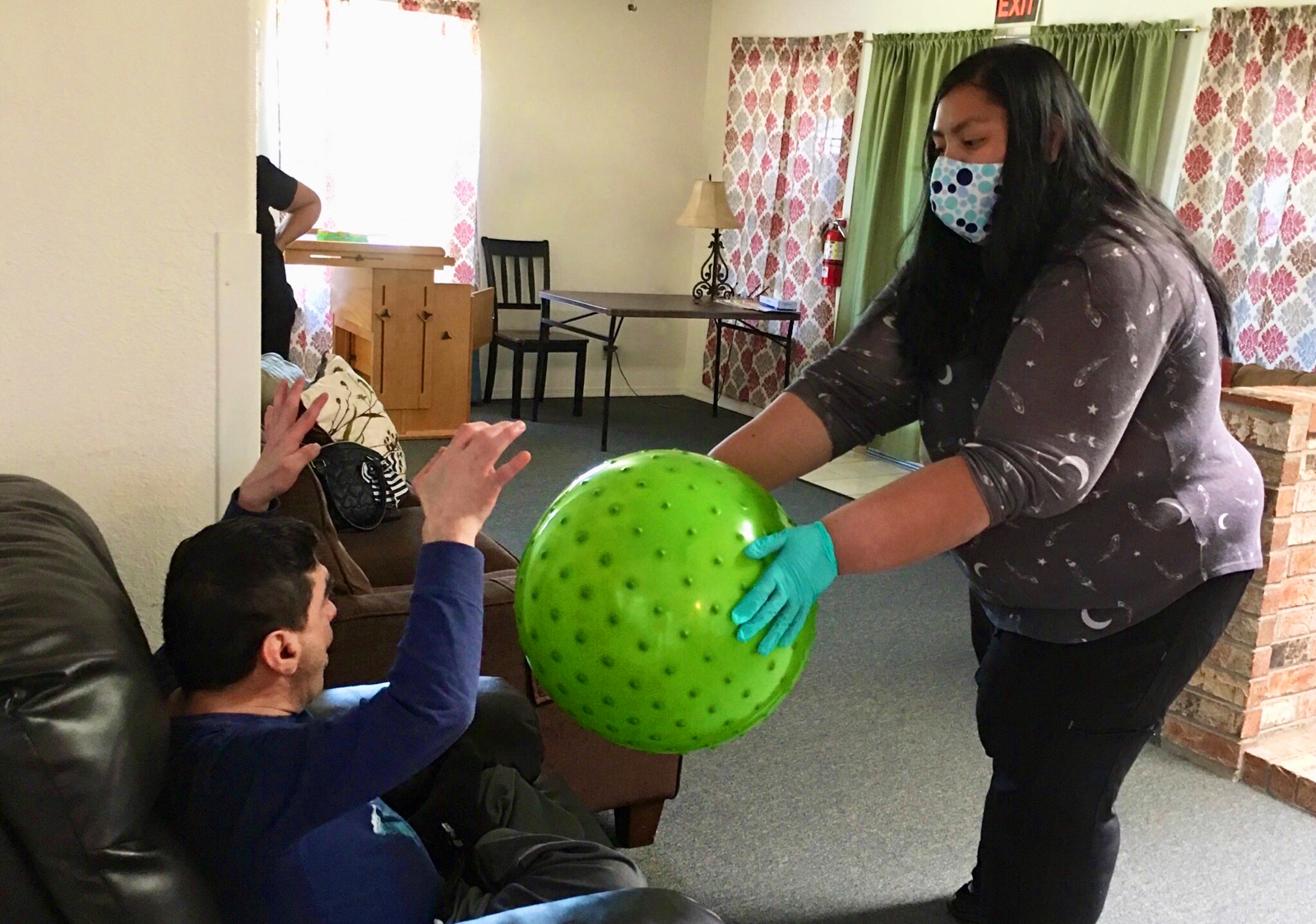 disabled man and Adelante support staff exercise with therapy ball