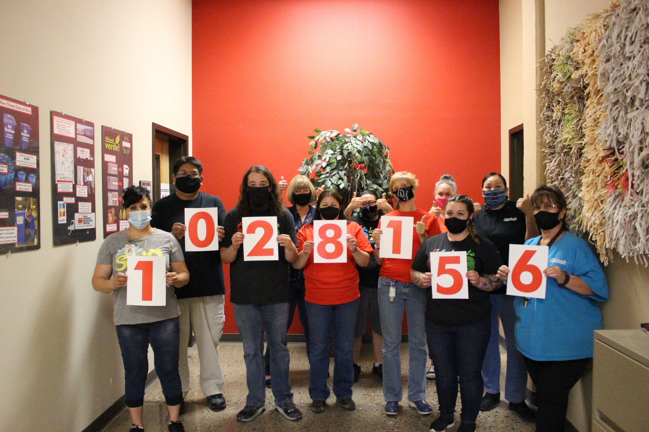 "A group of Adelante Document Imaging employees holding up number signs. The signs read ""1028156."""