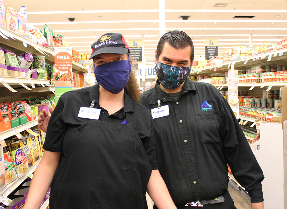 An Adelante client, a woman with a disability, poses with her supervisor in a grocery store aisle