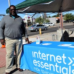 man from Comcast stands by table that says Internet Essentials