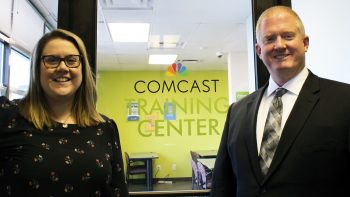 Comcast reps stand by the Comcast Training Center door with their logo, prior to the pandemic.
