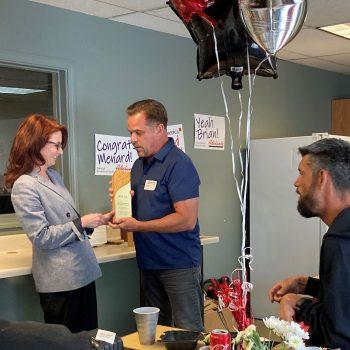 Brian Ammerman receives an award from Adelante CEO Rebecca Sanford